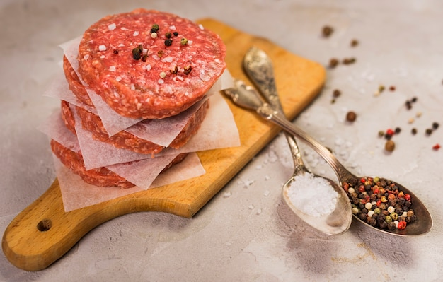 スプーンで木の板にパティのハンバーガー