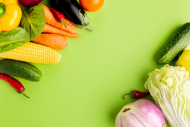 コピースペースを持つ緑の背景に野菜のトップビューの品揃え