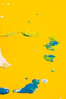 黄色の背景に青い絵の具の配置