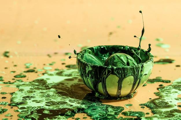 緑色の塗料スプラッシュとカップと抽象的な背景