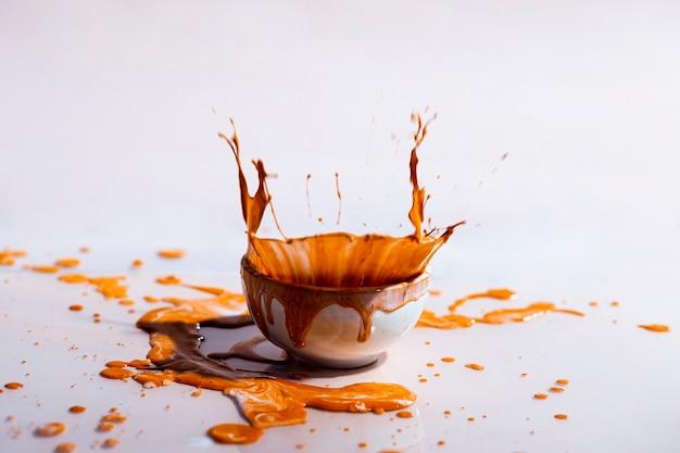 Коричневый всплеск краски и чашки абстрактный фон