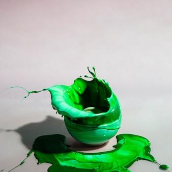緑のグラデーションペイントスプラッシュとカップの抽象的な背景