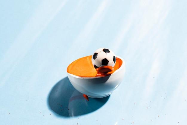 サッカーボールとオレンジ色の塗料スプラッシュ