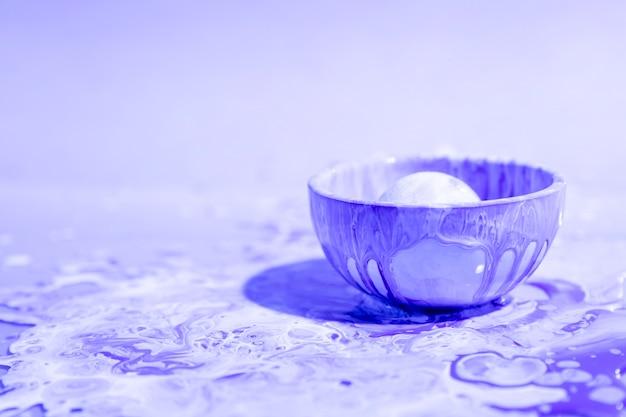 紫色の塗料の抽象的な背景と小さなカップ