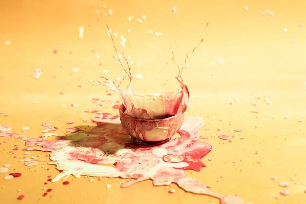 Маленькая чашка со смешанной краской абстрактного фона