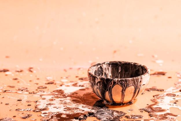 茶色の塗料の抽象的な背景と小さなカップ
