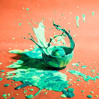 Чаша с зеленой краской и оранжевым фоном