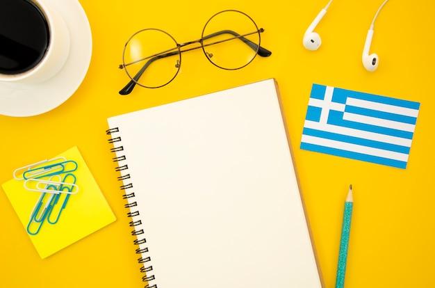 空のノートブックの横にあるギリシャの旗