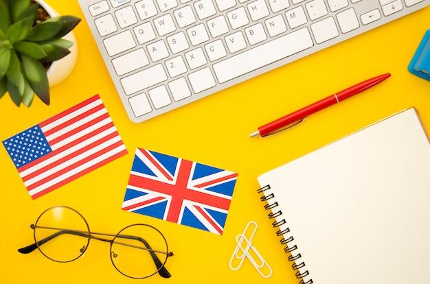 空のノートブックの横にあるアメリカとイギリスの国旗