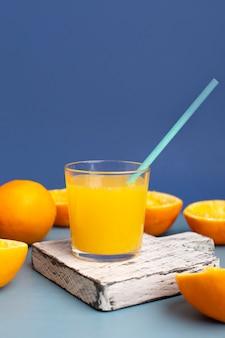 木造の底に正面のオレンジジュースのグラス
