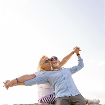 空中で腕を伸ばして幸せなカップル