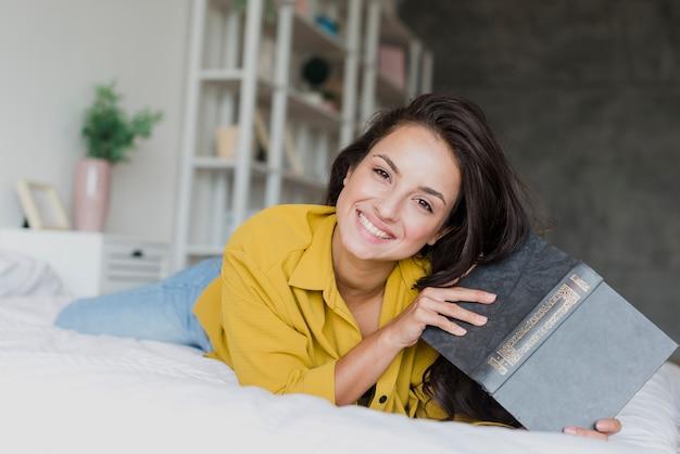 本とミディアムショットの幸せな女