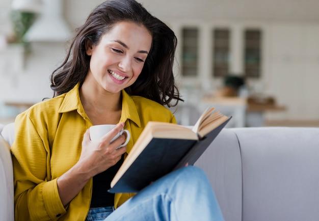 Средний снимок счастливая женщина с книгой и чашкой