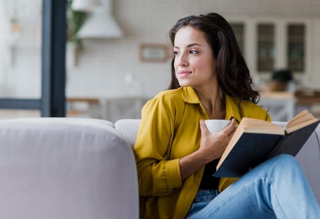 本とカップを持つミディアムショット女性