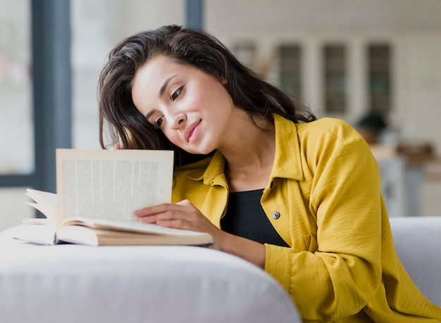 Вид сбоку женщина читает на диване