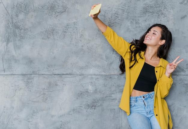 Средний снимок счастливая девушка делает селфи