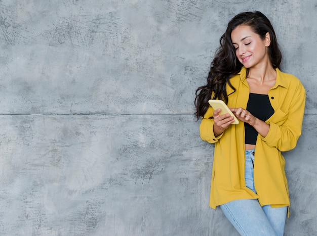携帯電話とセメントの背景を持つミディアムショット少女