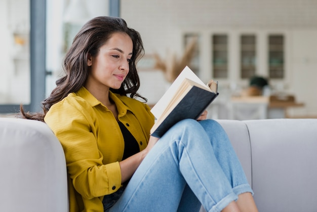 Боковой вид женщина читает в помещении