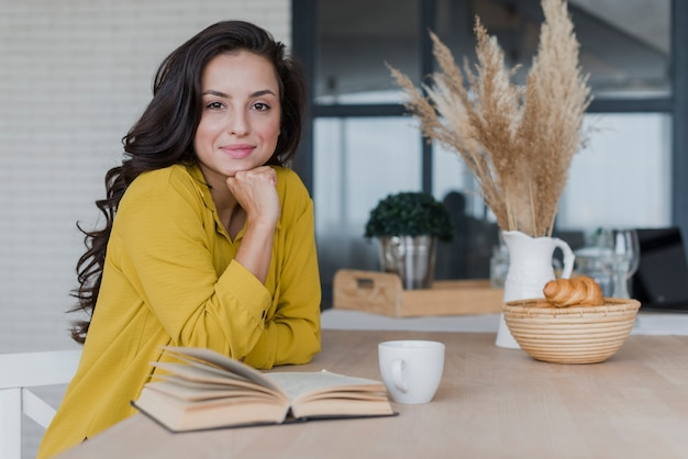 Средний выстрел красивая женщина с книгой и чашкой