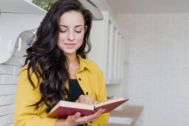 Средний снимок женщины с книгой с красной обложкой