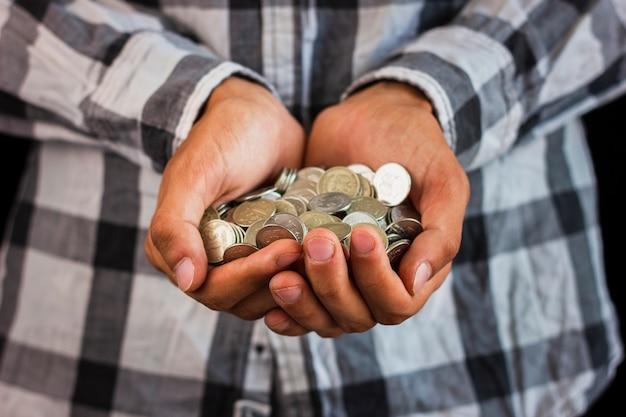 コインを節約の手で保持している男