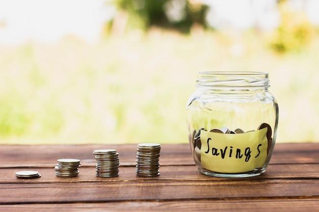 テーブルの上の貯金とコインスタックの瓶