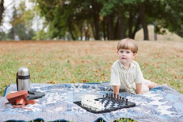 チェスをするピクニックで小さな男の子