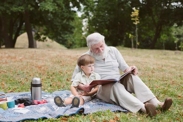 Дедушка с внуком на пикнике в парке