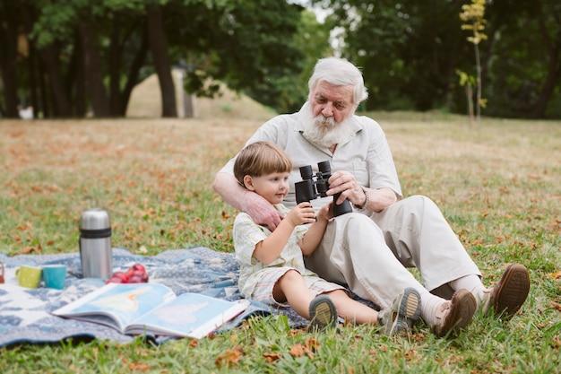 Дедушка показывает бинокль внуку