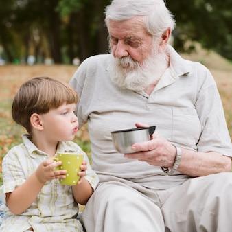フロントビューのおじいちゃんと孫がお茶を飲む