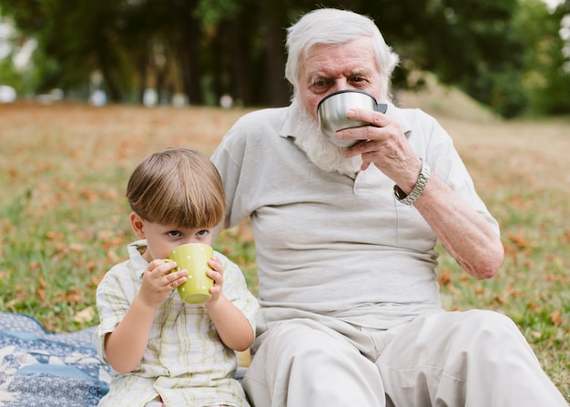 おじいちゃんと孫のピクニックでお茶を飲む
