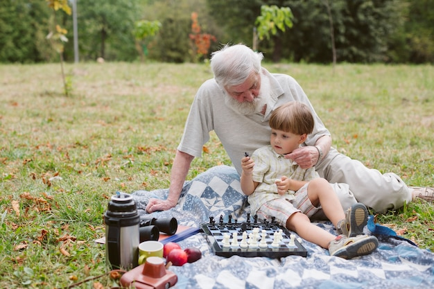 Дедушка обнимает внука и играет в шахматы