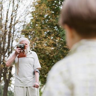 屋外で写真を撮る孫とおじいちゃん