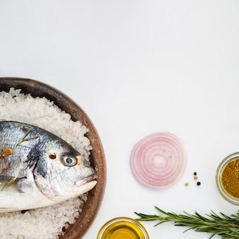 タマネギの横に氷の上に敷設する新鮮な魚