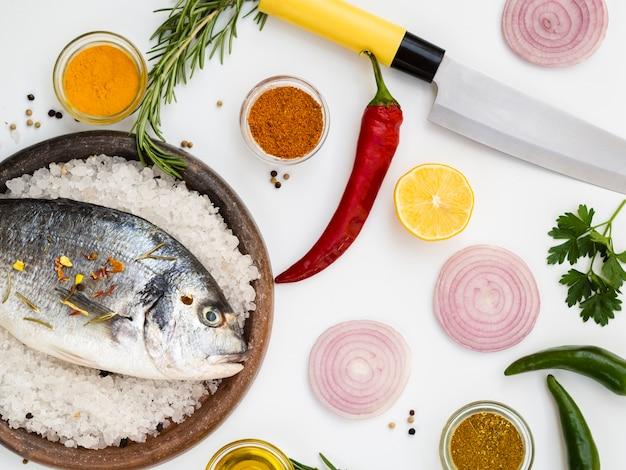 Свежая рыба в окружении ножа и овощей