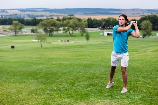 プロのゴルフコースでロングショットの男性ゴルフプレーヤー