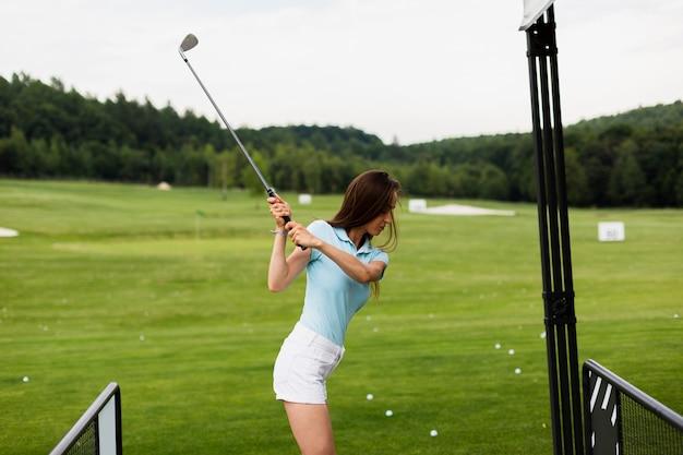 Женщина практикует гольф качели снаружи