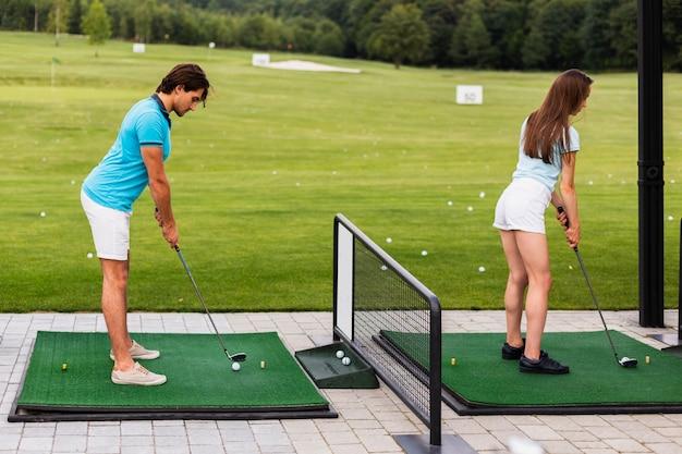 Задний вид игроков в гольф, практикующих свинг