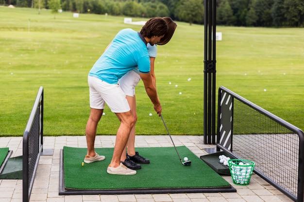 ゴルフの練習の女性はトレーナーと一緒に移動します