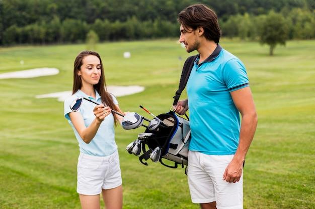 クラブを見ているゴルフプレーヤーの正面図