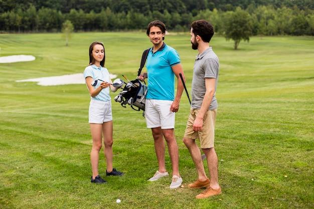 ゴルフコースで楽しんでいる友人のグループ