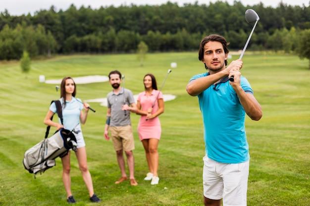 フィールドでゴルフをする友人