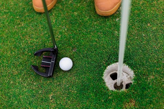 屋外でゴルフをする高角度の男