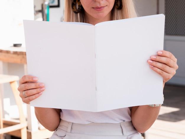Крупным планом женщина читает макет журнала