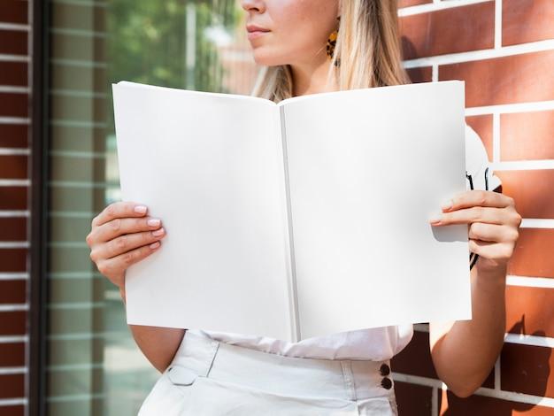 モックアップ雑誌を保持している女性