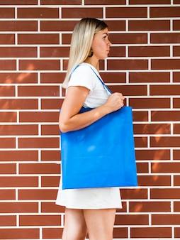 Женщина сбоку, держащая синюю сумку