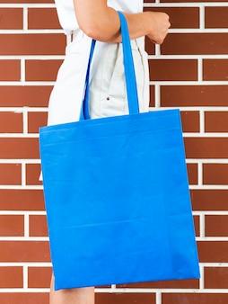 Вид сбоку женщина, держащая синий мешок макет