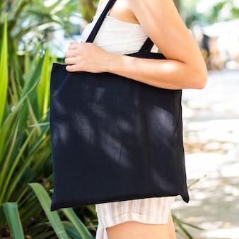 Боком женщина держит черную сумку