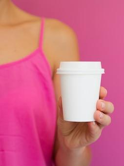 Крупным планом женщина с розовой рубашкой и чашкой