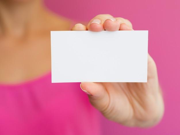 ピンクのシャツと白いカードでクローズアップ女性